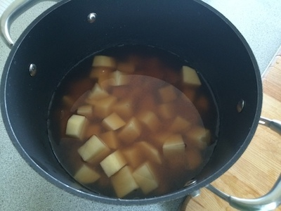 Potatoes and broth in pot